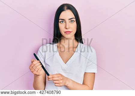 Beautiful woman with blue eyes using file nail relaxed with serious expression on face. simple and natural looking at the camera.
