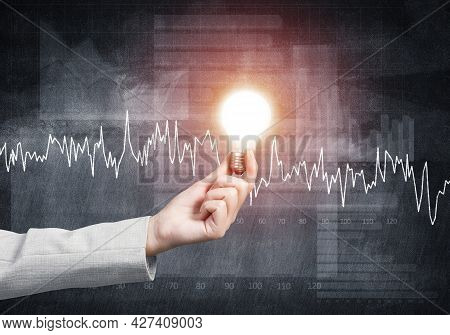 Human Hand With Glowing Incandescent Lamp On Grunge Background. Chart Of Stock Market Investment Tra