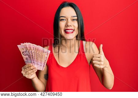 Young hispanic girl holding thai baht banknotes smiling happy and positive, thumb up doing excellent and approval sign