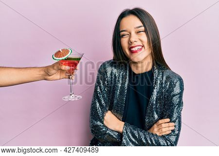 Young girl wearing sexy party jacket and hispanic arm offering cocktail happy face smiling with crossed arms looking at the camera. positive person.