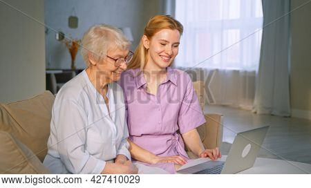 Young daughter and elderly mother talking to family on online conference using laptop