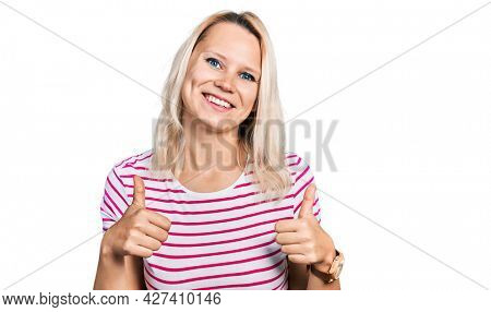 Young caucasian woman wearing casual clothes success sign doing positive gesture with hand, thumbs up smiling and happy. cheerful expression and winner gesture.