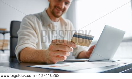 Smiling guy with beard pays company bills online holding yellow card and entering number on white laptop at table with papers