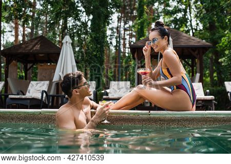 Positive Man Holding Glass Of Cocktail Near Girlfriend On Poolside