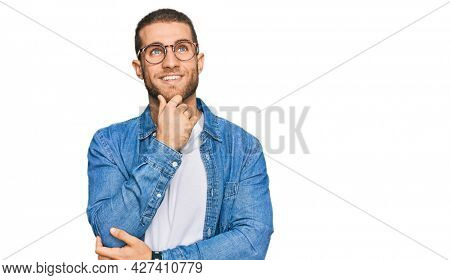 Young caucasian man wearing casual clothes with hand on chin thinking about question, pensive expression. smiling and thoughtful face. doubt concept.