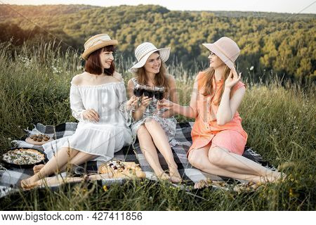 Close Up Outdoor Shot Of Three Gorgeous Smiling Girls, Clinking Glasses With Red Wine, Sitting On Ch