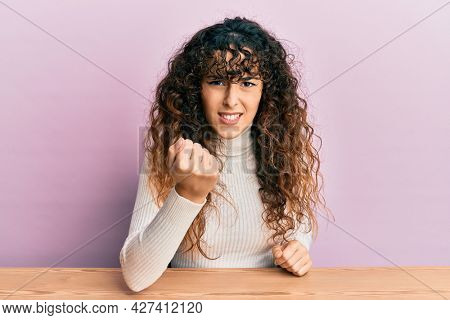 Young hispanic girl wearing casual clothes sitting on the table angry and mad raising fist frustrated and furious while shouting with anger. rage and aggressive concept.