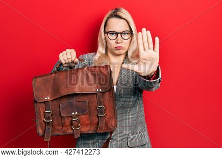 Beautiful caucasian blonde business woman wearing leather bag with open hand doing stop sign with serious and confident expression, defense gesture