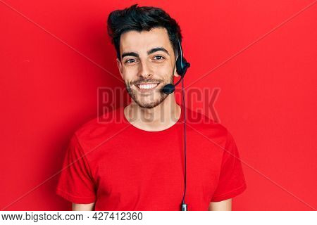 Young hispanic man wearing call center agent headset looking positive and happy standing and smiling with a confident smile showing teeth