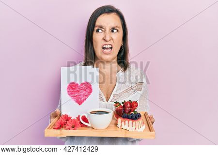 Middle age hispanic woman holding tray with breakfast food and heart draw angry and mad screaming frustrated and furious, shouting with anger. rage and aggressive concept.