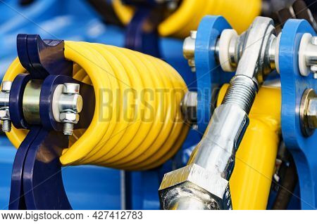 Big, Hard Made Of Steel Yellow Color Spring At Blue Heavy Machine. Machinery Industrial Detail