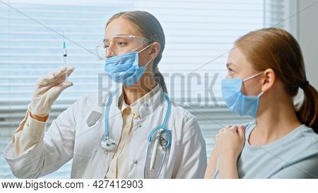 Professional lady general practitioner injects young woman patient in blue disposable face mask against hospital window close view