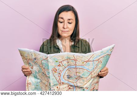 Middle age hispanic woman holding city map relaxed with serious expression on face. simple and natural looking at the camera.