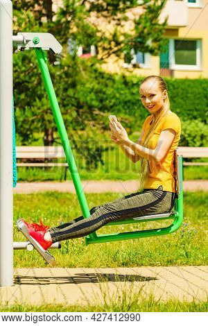 Young Woman Working Out In Outdoor Gym. Girl Holding Mobile Phone While Doing Exercises On Street Ma