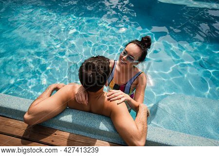 Overhead View Of Positive Woman Hugging Shirtless Man In Swimming Pool