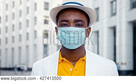 African American man in blue disposable face mask looks straight standing on street against highrise city building close view
