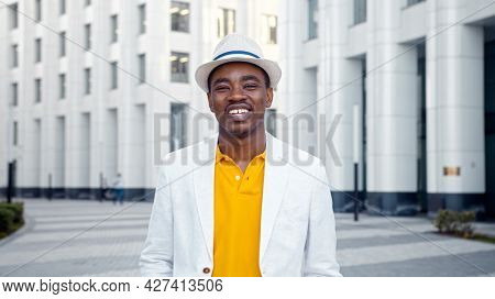Smiling African American businessman in white fedora hat with blue strip walks along city square with highrise city buildings closeup