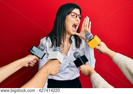 Young hispanic woman being interviewed for journalist hands with microphone shouting and screaming loud to side with hand on mouth. communication concept.