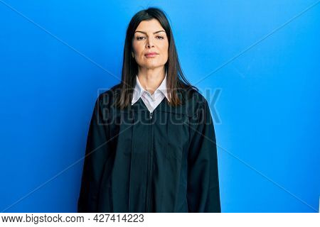 Young hispanic woman wearing judge uniform relaxed with serious expression on face. simple and natural looking at the camera.