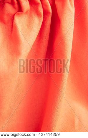 Beautiful Orange Fabric Texture With Folds And Contrasting Shadows . Draped Background Of Bright Cot