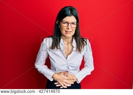 Young hispanic woman wearing business shirt and glasses with hand on stomach because indigestion, painful illness feeling unwell. ache concept.