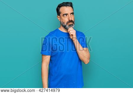 Middle aged man with beard wearing casual blue t shirt with hand on chin thinking about question, pensive expression. smiling with thoughtful face. doubt concept.