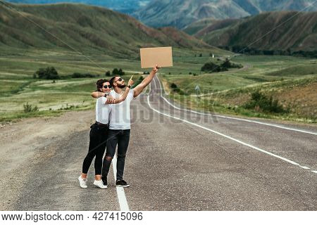 A Man And A Woman Are Hitchhiking. Wanderlust, Autostop Journey Concept. Young People Traveling Hitc