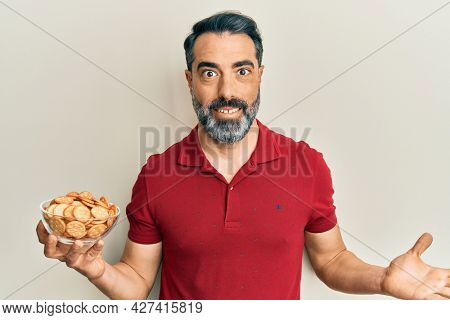 Middle age man with beard and grey hair holding bowl with salty crackers biscuits celebrating achievement with happy smile and winner expression with raised hand