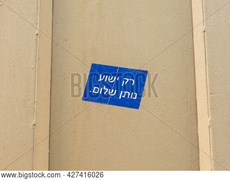 Blue Sticker With The Inscription In Hebrew - Only Jesus Gives Peace, Pasted On A Metal Fence Near T