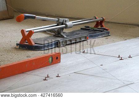 Measuring Level And Manual Tile Cutter On Porcelain Stoneware Floor