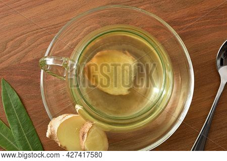 Detail Of Cup With Ginger Infusion On Wooden Table With Spoon And Leaves. Top View.