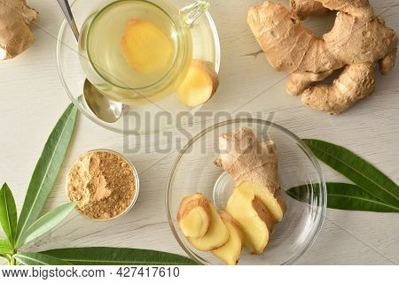 Hot Ginger-infused Cup On A White Table With Sliced Ginger Root In A Bowl. Top View.