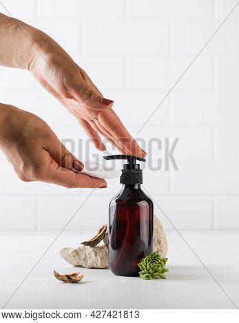 Womens Hands Press On A Glass Brown Dispenser With A Liquid Tonic. An Environmentally Friendly Produ