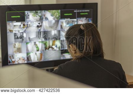 Security Guard Girl Sits In Front Of The Screen And Watches The Building On Video Surveillance. Soft