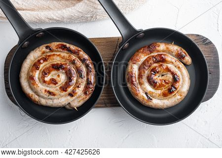 Grilled Pork Meat Sausages Set In Cast Iron Frying Pan, On White Background, Top View Flat Lay