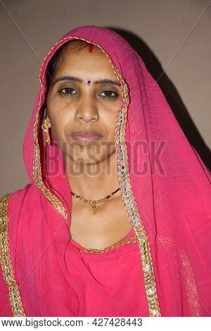 Indian Rural Woman Wearing A Pink Rajasthani Dress, Photo-shoot In The Village House