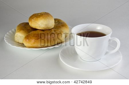 Patties on a plate and a cup of tea.