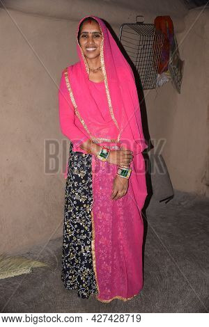 Indian Rural Woman Wearing A Pink Rajasthani Dress, Photo-shoot In The Village House.