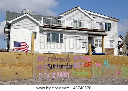 Signs in front of damaged beach house in devastated area after Hurricane Sandy