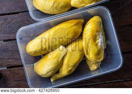 Overhead View Of Golden Yellow Musang King Durian Pulp Flesh In Container On Wooden Surface