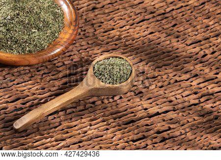 Artemisia Dracunculus - Dried Organic Tarragon Leaves In Wooden Spoon