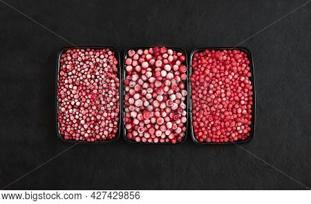 Set Of Frozen Berries On A Black Background. Cranberries, Red Currants And Cowberries In Plastic Con