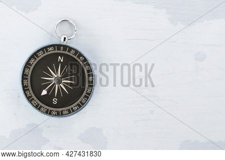 Old Classic Navigation Compass On Blue Vintage Background With Scratches And Cracks In Paint As Symb