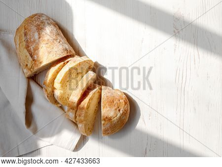 Sliced Organic Bread Ciabatta With Vintage Linen Napkin On White Wooden Background. Top View Of Home
