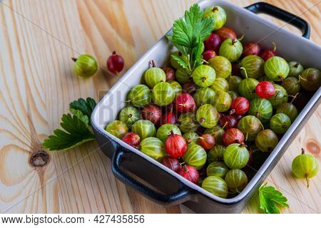Red And Green Gooseberries In A Ceramic Form On A Light Wooden Background. Cooking Ingredients. Goos