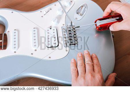 Guitar Master Adjusting Bridge Saddle On Tremolo Of Electric Guitar Using Multitool, Close Up Shot O