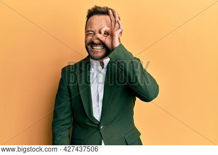 Middle age man wearing business suit doing ok gesture with hand smiling, eye looking through fingers with happy face.