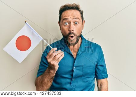 Middle age man holding japan flag scared and amazed with open mouth for surprise, disbelief face