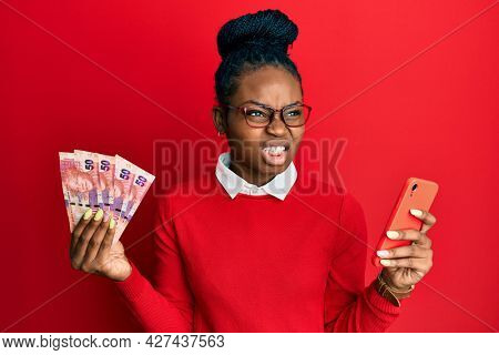 Young african american woman using smartphone holding south africa rand banknotes angry and mad screaming frustrated and furious, shouting with anger. rage and aggressive concept.