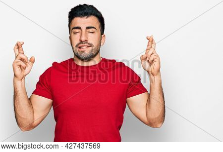 Hispanic man with beard wearing casual red t shirt gesturing finger crossed smiling with hope and eyes closed. luck and superstitious concept.